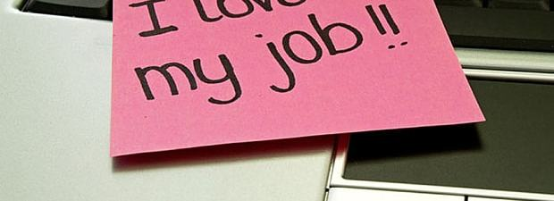 pink post it note sitting on top of an open laptop with the printing I love my job