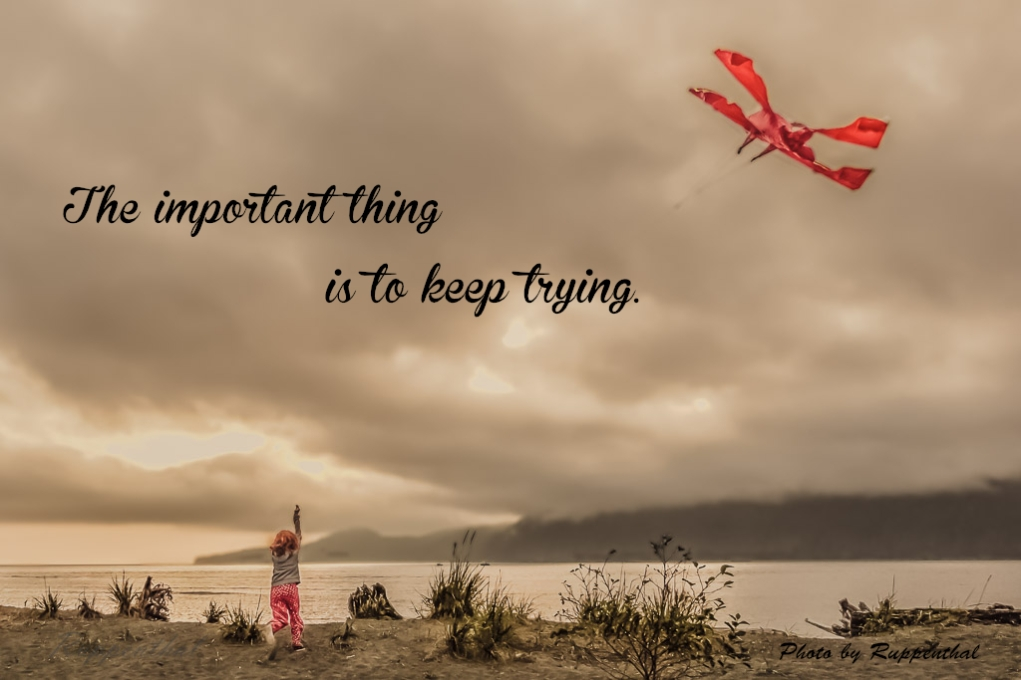 Young red headed girl wearing red pajamas flying a red kite on a beach near the ocean