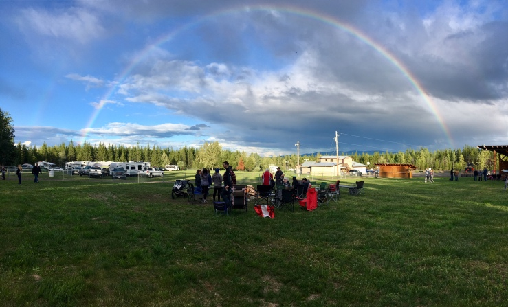 A full rainbow in front of a cloudy sky covering the field like a dome, with family members inside that dome.