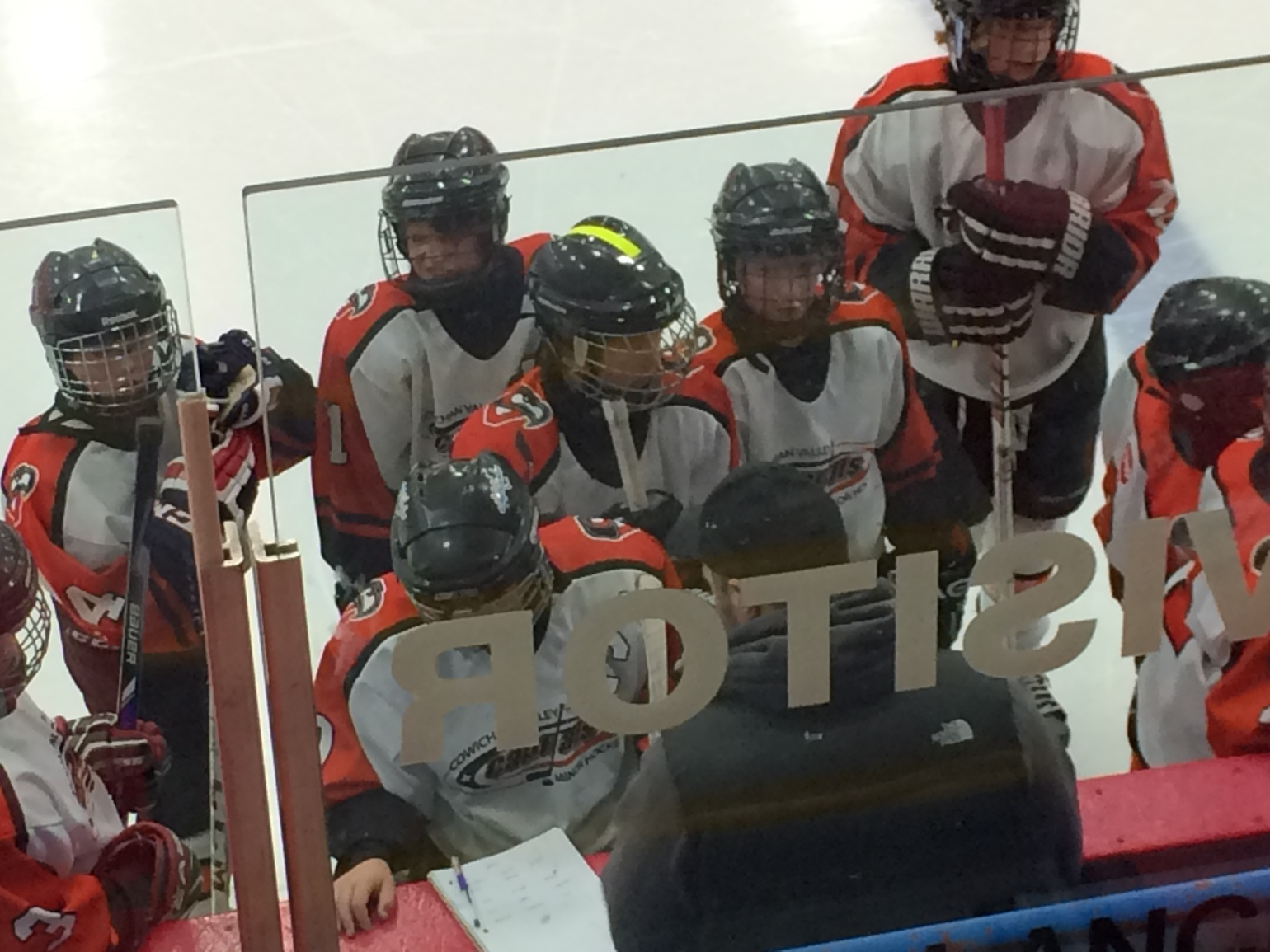 young hockey players wearing white and orange jerseys and black helmets. One player in the middle has a lime green stripe on the top of his helmet. They are gathered around the coach who is explaining what to do next.