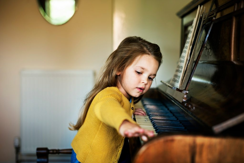 young girl sitting beside a piano playing with the keys